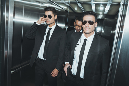 two bodyguards and politician standing in elevator Stock Photo
