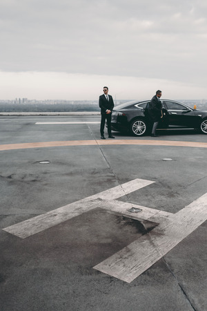 bodyguard and businessman standing near car on helipad