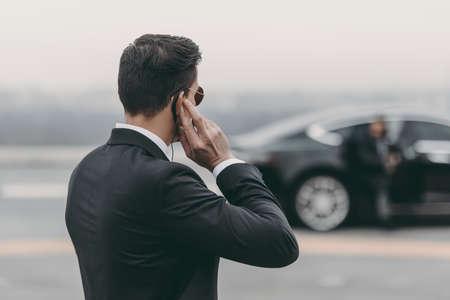 knappe bodyguard staand en luisterend bericht met veiligheidsoortje op helikopterplatform Stockfoto