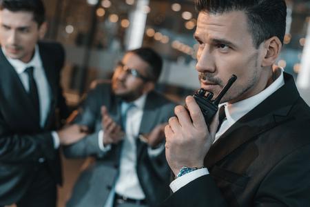 security guard talking by portable radio about male suspect Foto de archivo - 104556356