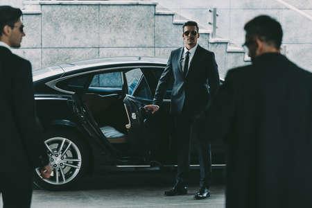 Leibwächter in der Sonnenbrille, die Autotür zum Geschäftsmann öffnet