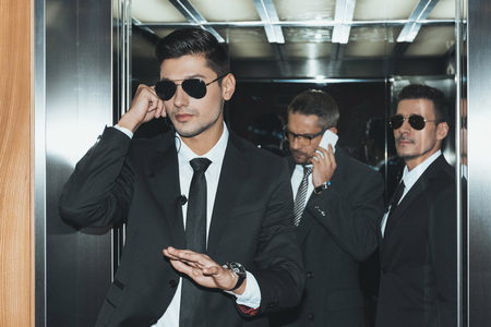 bodyguard listening security earpiece and businessman talking by smartphone Reklamní fotografie