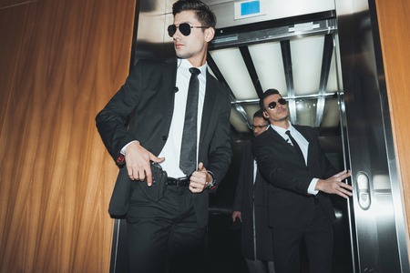bodyguard putting hand on gun when going out with businessman from elevator