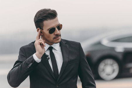 handsome bodyguard listening message with security earpiece Stock Photo
