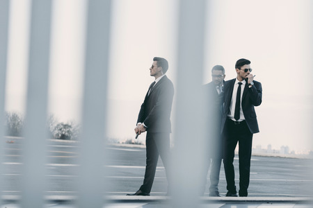 view through fence of businessman with bodyguards standing on helipad Stock Photo