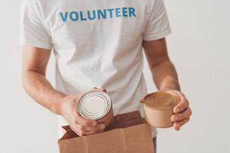 cropped shot of volunteer putting tin cans in paper bag Standard-Bild - 104556494