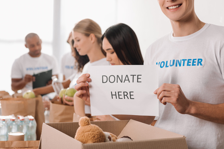 cropped shot of volunteer holding charity placard with blurred colleagues working on background Standard-Bild - 104556315