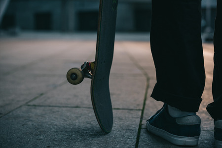 cropped shot of skateboarder standing with board Stock Photo