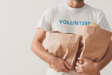 cropped shot of volunteer with paper bags of goods