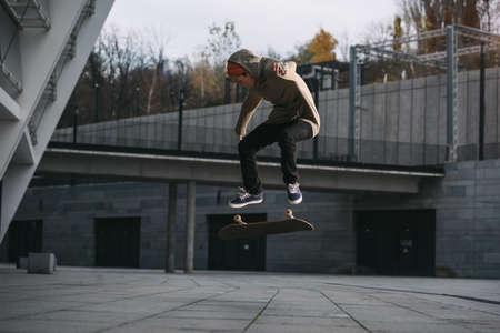 Joven skater realizar truco de salto en ubicación urbana