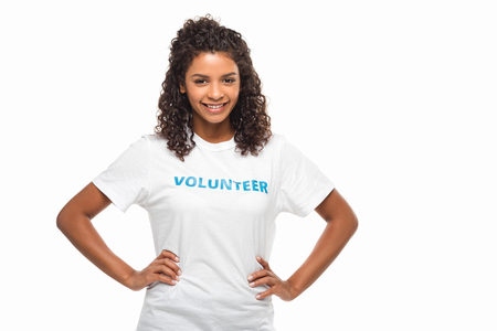 female african american volunteer with arms akimbo isolated on white