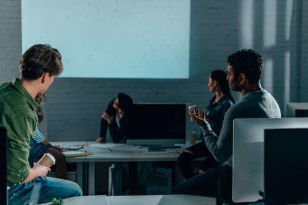 gente viendo la presentación en la oficina por la noche. pantalla en blanco Foto de archivo