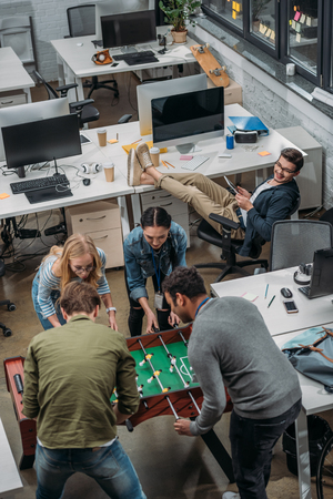 multicultural people playing in table soccer at modern office Stock Photo