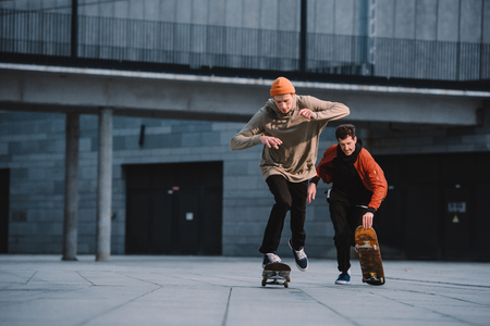 stylish young men in streetwear outfit riding skateboards Stok Fotoğraf