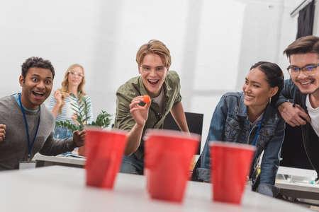 Jeunes gens attrayants jouant de la bière pong au bureau moderne après le travail