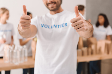 cropped shot of handsome volunteer showing thumbs up with blurred colleagues working on background