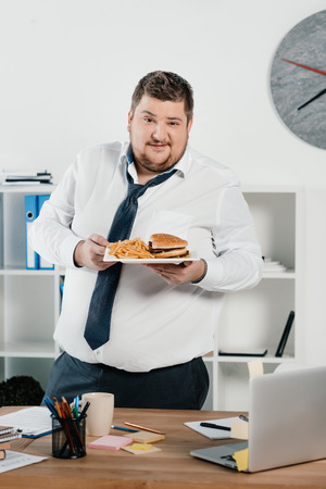 overweight businessman with junk food in office Banco de Imagens