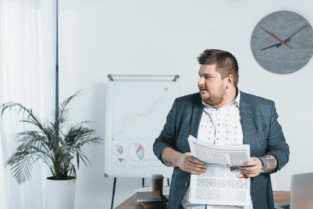 overweight businessman in suit reading newspaper in office Banco de Imagens