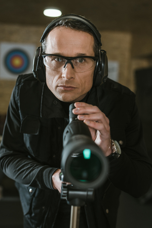 handsome man with binoculars in shooting range