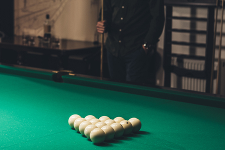 cropped image of man standing behind of gambling billiard table with set of russian pool balls Stock Photo