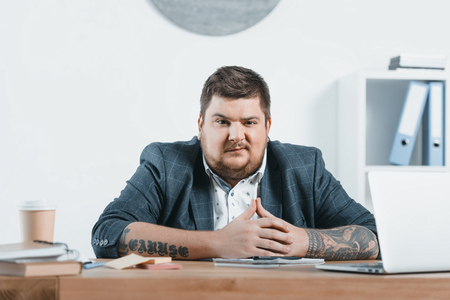 confident overweight businessman sitting at workplace in office