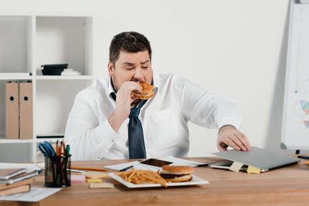 übergewichtiger Geschäftsmann, der Hamburger isst und Laptop im Büro benutzt Standard-Bild