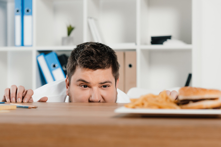 overweight businessman looking at hamburger and french fries at workplace Imagens