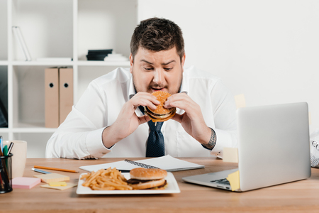 overweight businessman eating junk food in office Banco de Imagens
