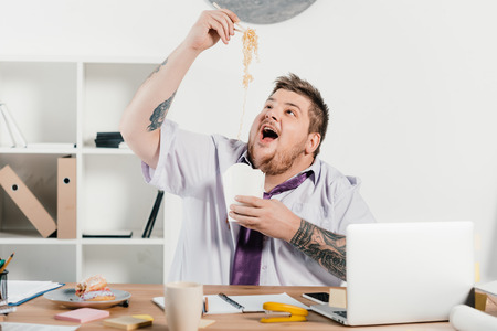 excited overweight businessman eating noodles at workplace in office Banco de Imagens