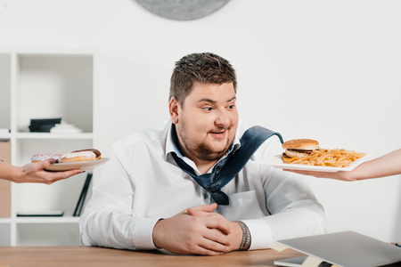 overweight businessman choosing donuts or hamburger with french fries for lunch Banco de Imagens