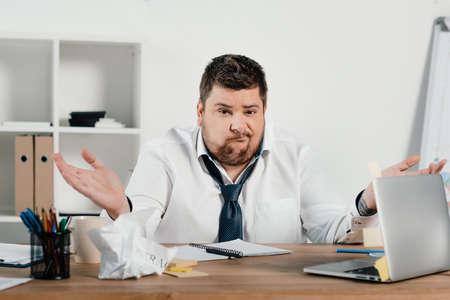 Confundido empresario con sobrepeso sentado en el espacio de trabajo con documentos y portátil Foto de archivo