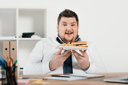 excited overweight businessman with hamburger and french fries in office