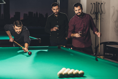 successful handsome man playing in pool at bar with friends Stock Photo