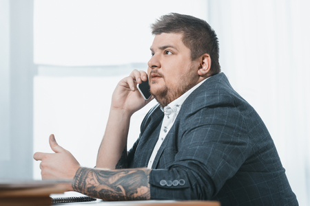 fat businessman talking on smartphone in office Banco de Imagens