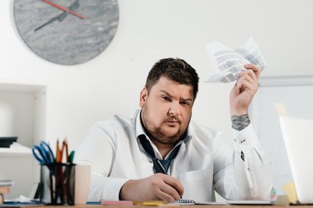 overweight businessman writing and doing paperwork in office