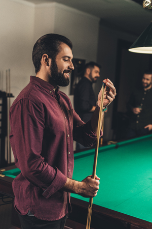 handsome man rubbing cue with chalk at bar with friends Archivio Fotografico - 104558853