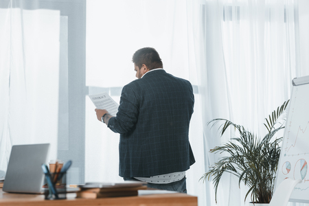 back view of overweight businessman in suit reading document at window in office Banco de Imagens