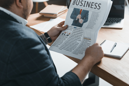 cropped view of overweight businessman reading business newspaper at workplace