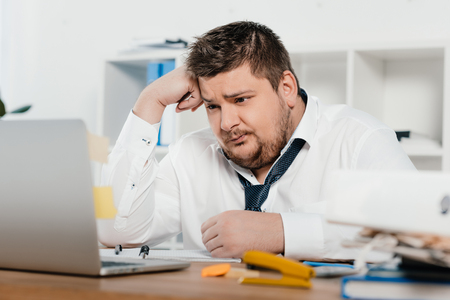 confused overweight businessman working with laptop in office Archivio Fotografico