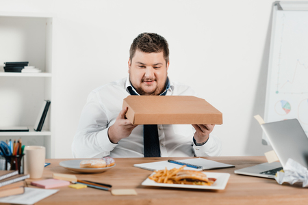 overweight businessman eating pizza at workplace