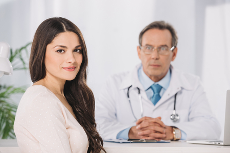 attractive female patient sitting at clinic and looking at camera Stockfoto