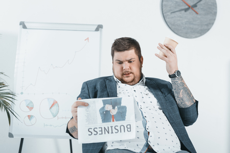 overweight businessman drinking coffee and reading business newspaper in office