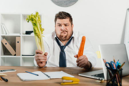 confused overweight businessman looking at fresh vegetables