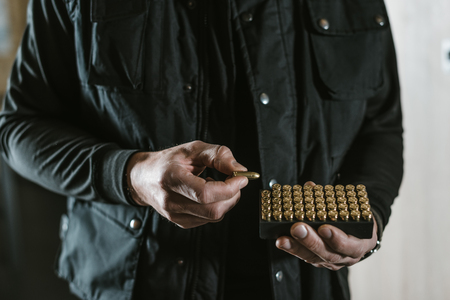 cropped image of man taking bullet from box