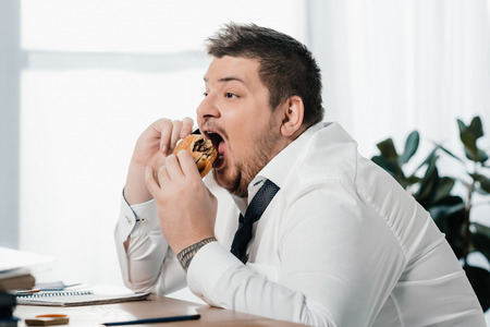 fat businessman talking on smartphone while eating hamburger in office