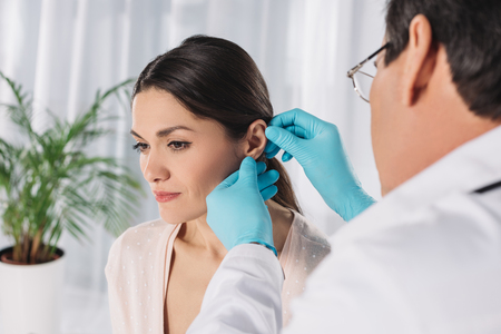 cropped image of doctor examining female patient ear