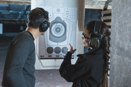 shooting instructor pointing on used target in shooting range Standard-Bild
