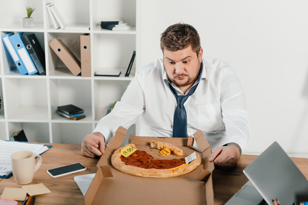overweight businessman looking at pizza while sitting in office Banco de Imagens