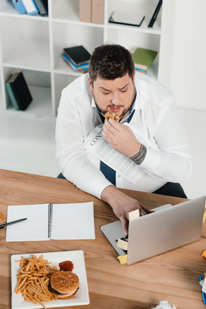 overweight businessman eating junk food while working with laptop in office Banco de Imagens