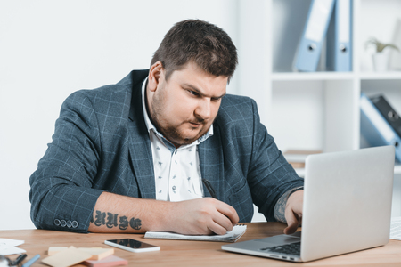overweight businessman in suit writing and working with laptop at workplace Banco de Imagens